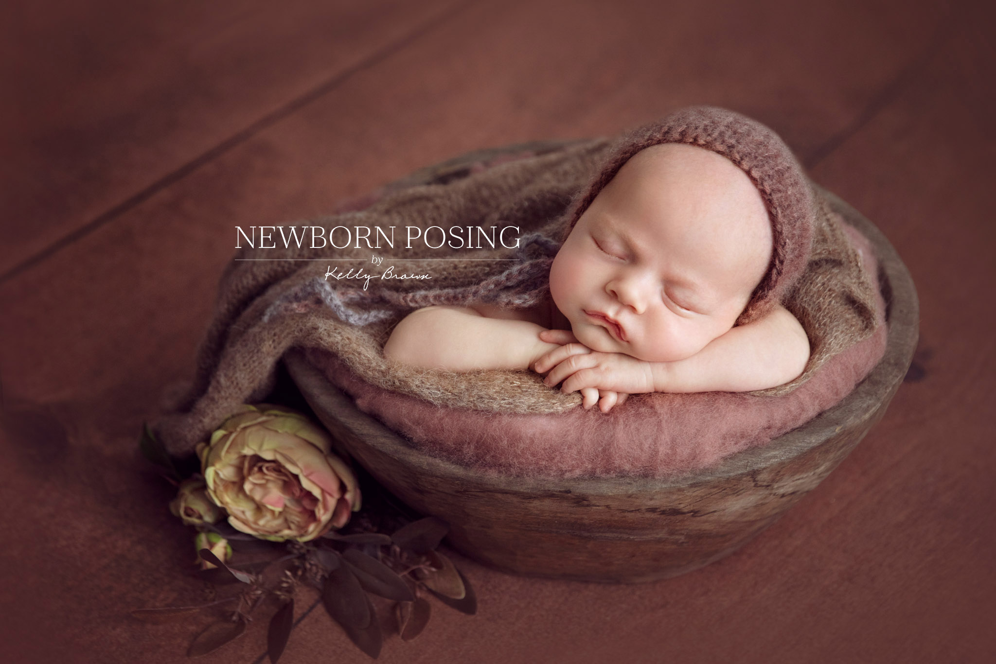 Newborn photography of baby head resting on hands in prop